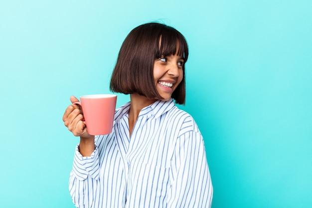 Молодая женщина смешанной расы, держащая розовую кружку, изолированную на синем фоне, смотрит в сторону, улыбаясь, веселая и приятная.