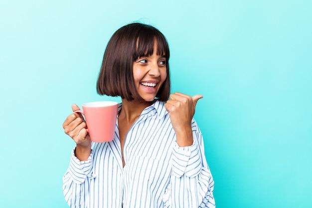 Молодая женщина смешанной расы, держащая розовую кружку, изолированную на синем фоне, указывает пальцем далеко, смеясь и беззаботно.