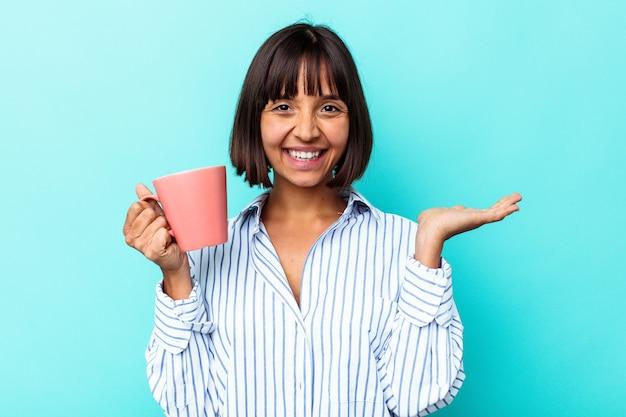 Молодая женщина смешанной расы, держащая розовую кружку, изолированную на синем фоне, показывает пространство для копии на ладони и держит другую руку на талии.
