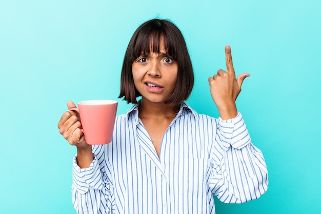 Молодая женщина смешанной расы, держащая розовую кружку, изолированную на синем фоне, показывая жест разочарования указательным пальцем.