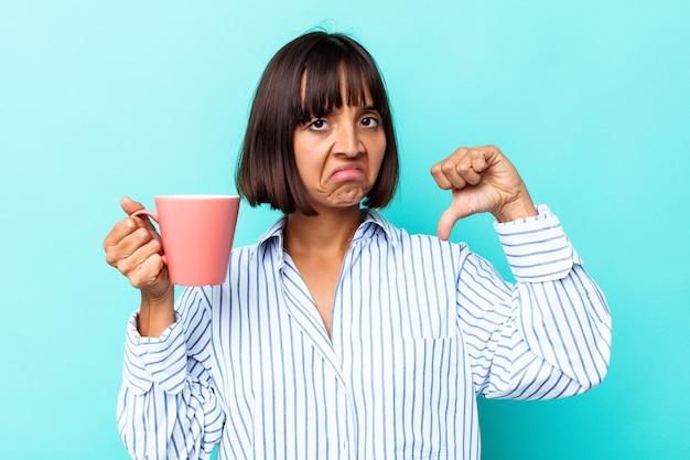 Молодая женщина смешанной расы, держащая розовую кружку, изолированную на синем фоне, показывает жест неприязни, пальцы вниз. концепция несогласия.