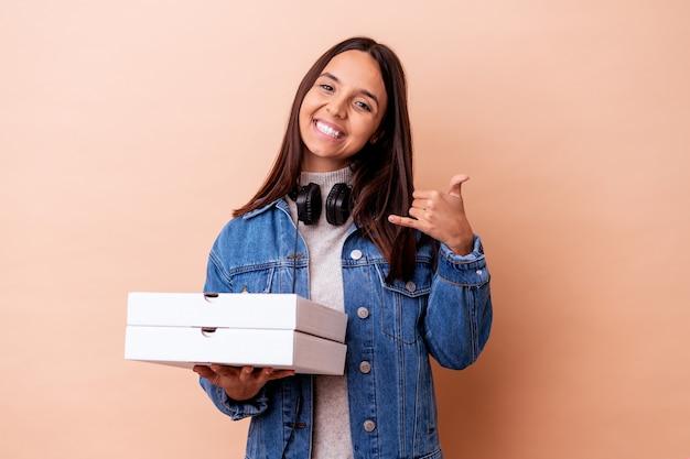 Молодая женщина смешанной расы, держащая изолированную пиццу, показывающая жест звонка по мобильному телефону с пальцами.