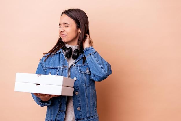 頭の後ろに触れて、考えて、選択をする孤立したピザを持っている若い混血の女性。