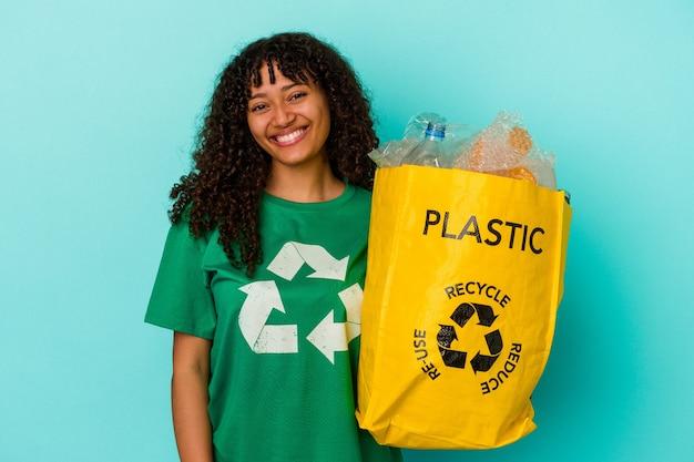 Молодая женщина смешанной расы, держащая переработанный полиэтиленовый пакет на синем фоне, счастливая, улыбающаяся и веселая.