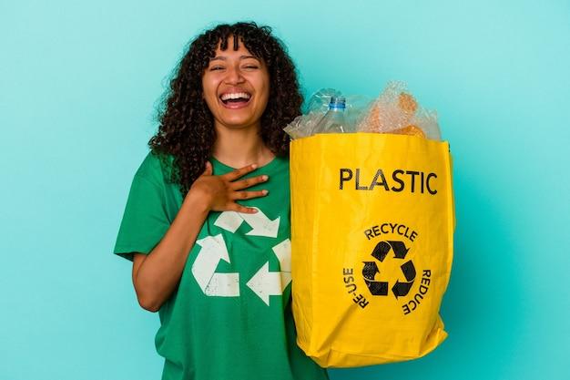 Молодая женщина смешанной расы, держащая переработанный полиэтиленовый пакет, изолированный на синем фоне, громко смеется, держа руку на груди.