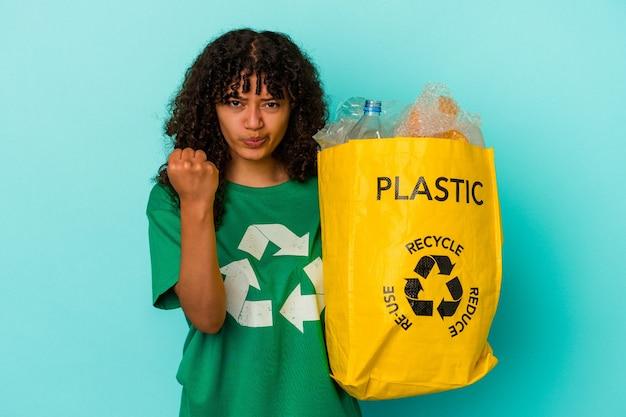 Молодая женщина смешанной расы, держащая переработанный полиэтиленовый пакет, изолированный на синем фоне, показывает кулак в камеру, агрессивное выражение лица.