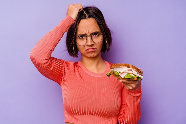 ショックを受けている紫色の背景に分離されたサンドイッチを保持している若い混血の女性、彼女は重要な会議を思い出しました。