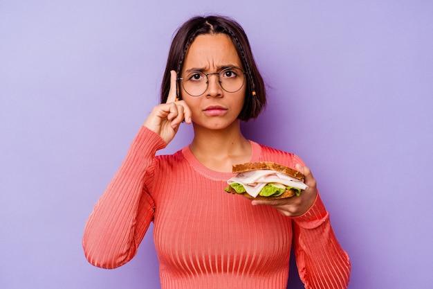 Молодая женщина смешанной расы, держащая сэндвич, изолированные на фиолетовом фоне, указывая висок пальцем, думая, сосредоточилась на задаче.