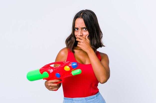 心配そうに見える手で口を覆って孤立した水鉄砲を保持している若い混血の女性。