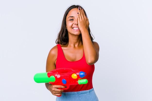 手のひらで顔の半分を覆うことを楽しんで孤立した水鉄砲を保持している若い混血の女性。