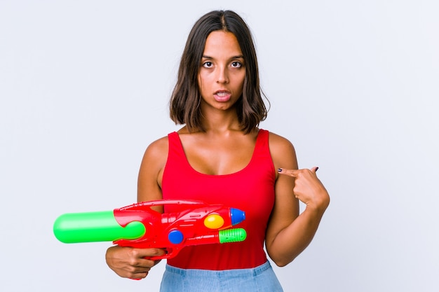 孤立した水鉄砲を持っている若い混血の女性は、指でポイントを下に向け、前向きな気持ちです。