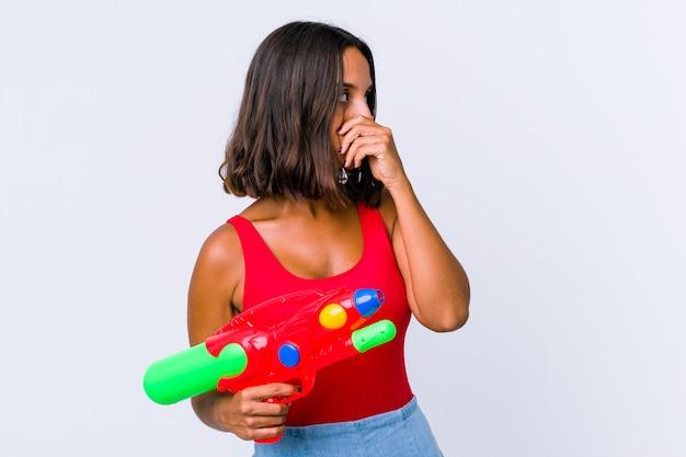 水鉄砲を持っている若い混血の女性は、手で口を覆っているコピースペースを見て思慮深く孤立しました。