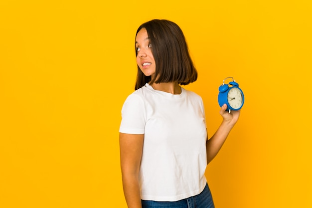 Young mixed race woman holding an alarm clock isolated