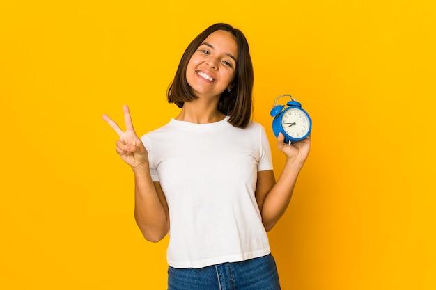 Young mixed race woman holding an alarm clock