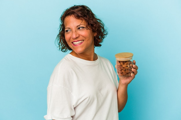 Young mixed race woman holding an almond jar isolated on blue background looks aside smiling, cheerful and pleasant.
