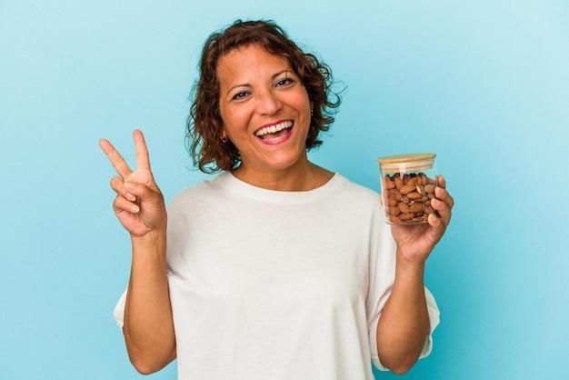 青い背景に分離されたアーモンドの瓶を持っている若い混血の女性は、指で平和のシンボルを喜んで気楽に示しています。
