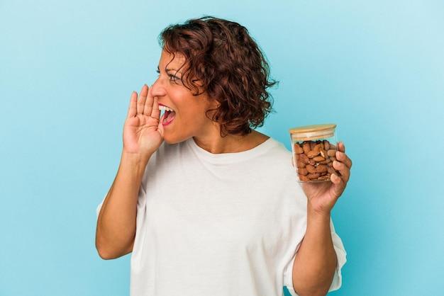 青い背景に分離されたアーモンドの瓶を持って叫び、開いた口の近くで手のひらを保持している若い混血の女性。