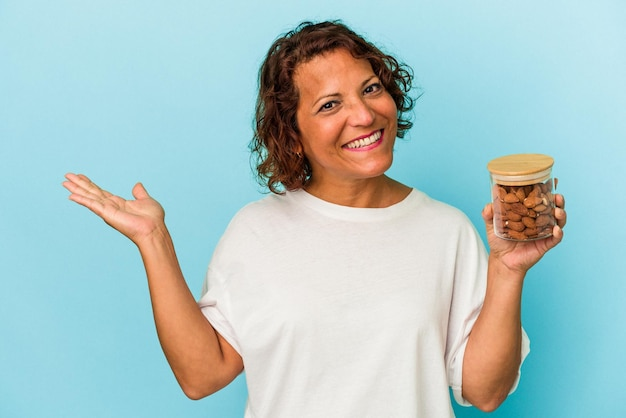 手のひらにコピースペースを示し、腰に別の手を保持している青い背景に分離されたアーモンドの瓶を保持している若い混血の女性。