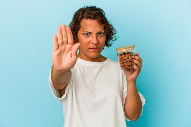青の背景に分離されたアーモンドの瓶を持って、一時停止の標識を示す伸ばした手で立っている若い混血の女性は、あなたを防ぎます。