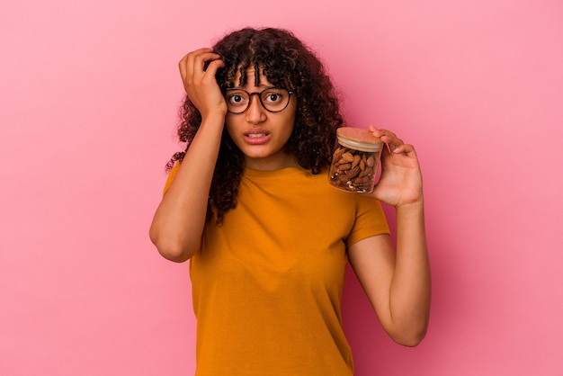 ピンクの背景に分離されたアーモンドの瓶を持っている若い混血の女性はショックを受けて、彼女は重要な会議を思い出しました。