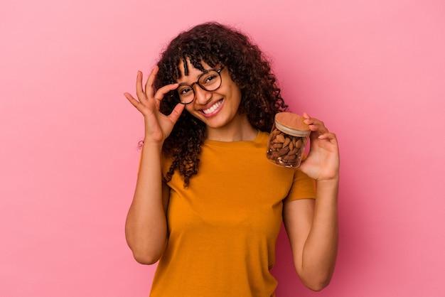 ピンクの背景に分離されたアーモンドの瓶を保持している若い混血の女性は、目に大丈夫なジェスチャーを維持して興奮しました。