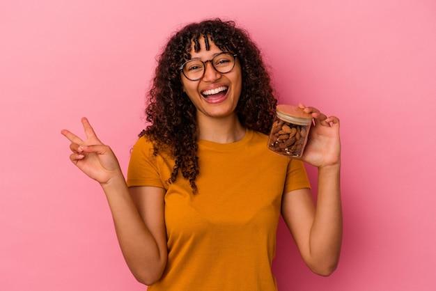 ピンクの背景に分離されたアーモンドの瓶を持っている若い混血の女性は、指で平和のシンボルを喜んで気楽に示しています。