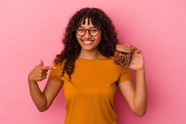 ピンクの背景に分離されたアーモンドの瓶を持っている若い混血の女性がシャツのコピースペースを手で指している、誇りと自信を持って