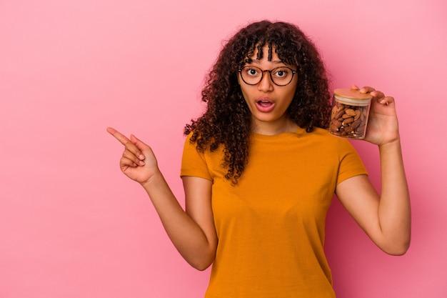 側面を指しているピンクの背景に分離されたアーモンドの瓶を保持している若い混血の女性