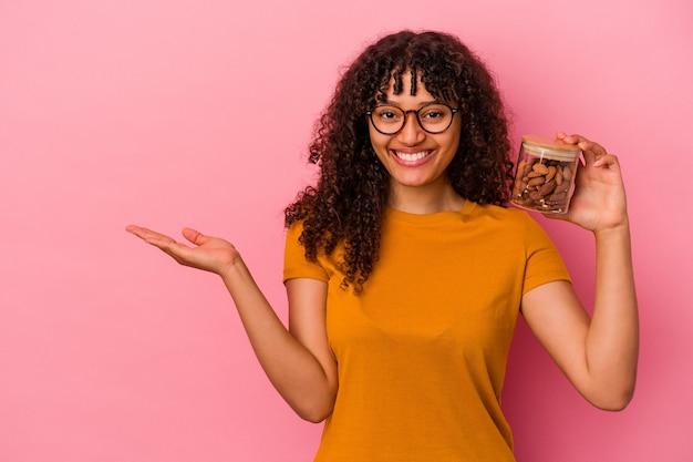 ピンクの背景に分離されたアーモンドの瓶を保持し、手のひらにコピースペースを示し、腰に別の手を保持している若い混血の女性。