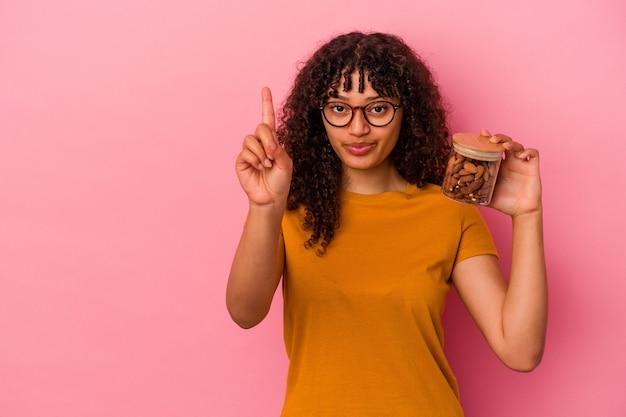 ピンクの背景に分離されたアーモンドの瓶を持っている若い混血の女性は、指でナンバーワンを示しています。
