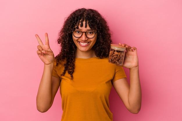 Молодая женщина смешанной расы, держащая миндальную банку, изолированную на розовом фоне, показывает номер два пальцами.