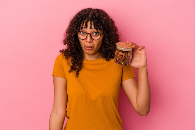 Молодая женщина смешанной расы, держащая миндальную банку, изолированную на розовом фоне, пожимает плечами и смущает открытые глаза.