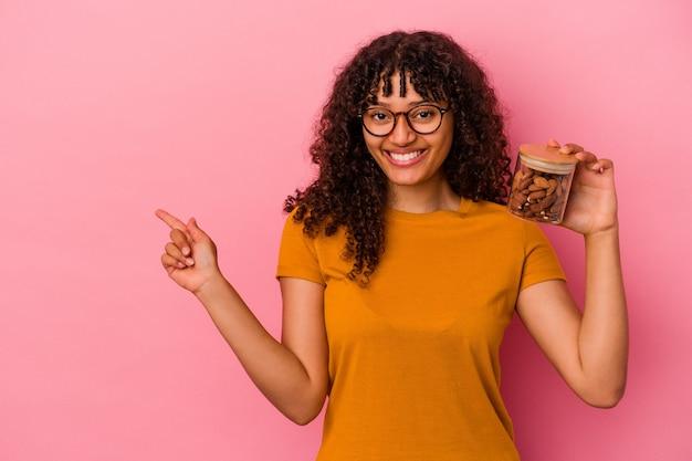 ピンクの背景に分離されたアーモンドの瓶を持って笑顔で脇を指して、空白のスペースで何かを示している若い混血の女性。