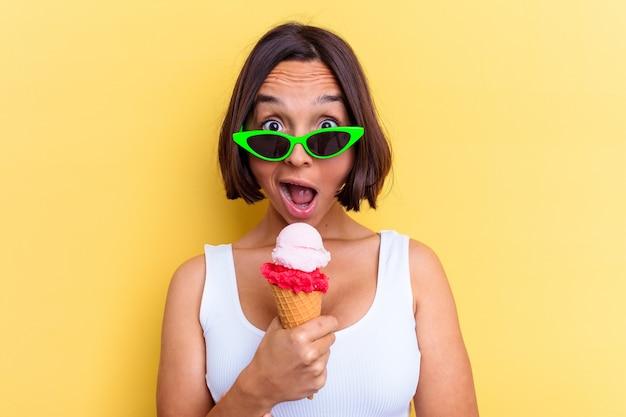 Молодая женщина смешанной расы, держащая мороженое, изолированную на желтом фоне