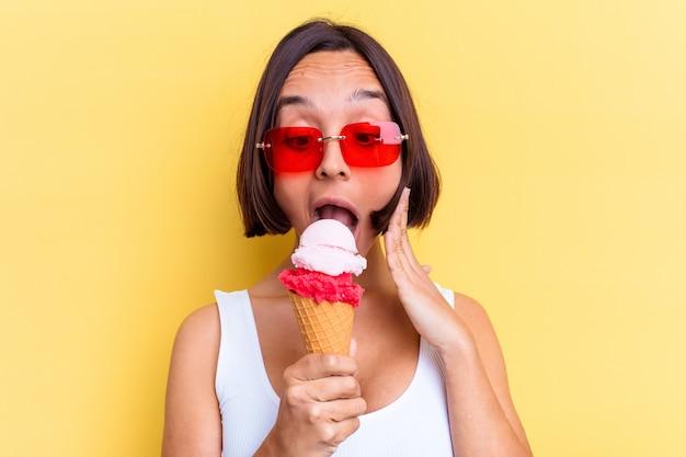 黄色の背景で隔離のアイスクリームを保持している若い混血の女性