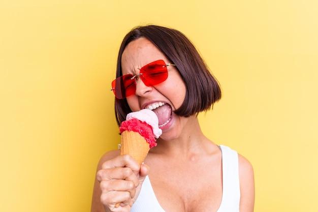 노란색 벽에 고립 된 아이스크림을 들고 젊은 혼혈 여자