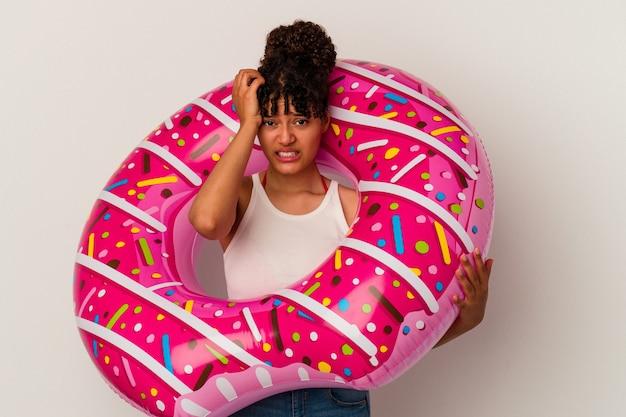 충격을 받고 흰색 배경에 고립 된 풍선 공기 도넛을 들고 젊은 혼합 된 인종 여자, 그녀는 중요한 회의를 기억했다.