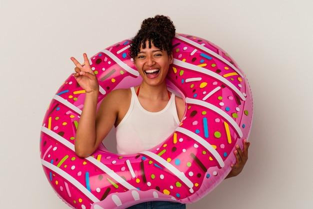 손가락으로 평화 기호를 보여주는 즐겁고 평온한 흰색 배경에 고립 된 풍선 공기 도넛을 들고 젊은 혼혈 여자.