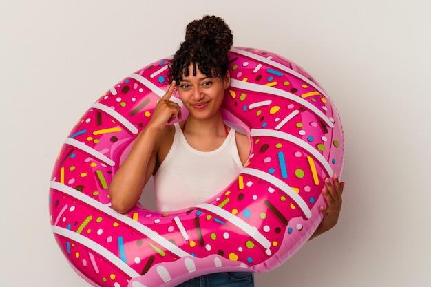 Молодая женщина смешанной расы, держащая надувной воздушный пончик на белом фоне, указывая висок пальцем, думая, сосредоточилась на задаче.