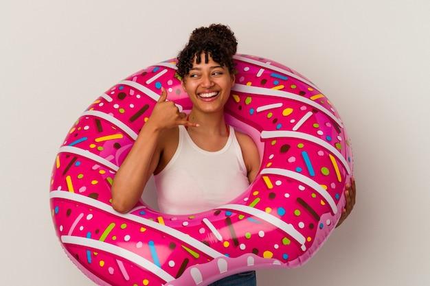 손가락으로 휴대 전화 제스처를 보여주는 흰색 배경에 고립 된 풍선 공기 도넛을 들고 젊은 혼합 된 인종 여자.