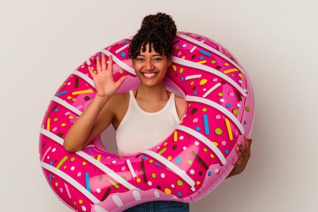손가락으로 명랑 게재 번호 5 웃 고 흰 벽에 고립 된 풍선 공기 도넛을 들고 젊은 혼합 된 경주 여자.