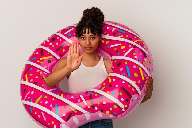당신을 방지, 정지 신호를 보여주는 뻗은 손으로 서 흰 벽에 고립 된 풍선 공기 도넛을 들고 젊은 혼합 된 인종 여자.