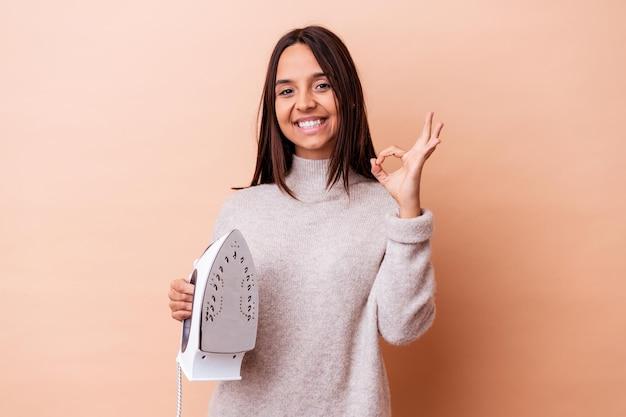 鉄を持っている若い混血の女性は、陽気で自信を持って大丈夫なジェスチャーを示しています。
