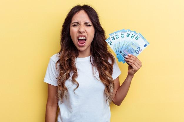 Молодая женщина смешанной расы, держащая счета, изолированные на желтом фоне, кричала очень сердито и агрессивно.