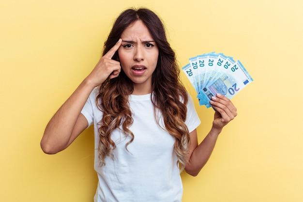 Молодая женщина смешанной расы, держащая счета, изолированные на желтом фоне, показывая жест разочарования с указательным пальцем.