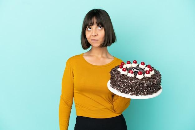 Молодая женщина смешанной расы держит торт ко дню рождения и смотрит вверх