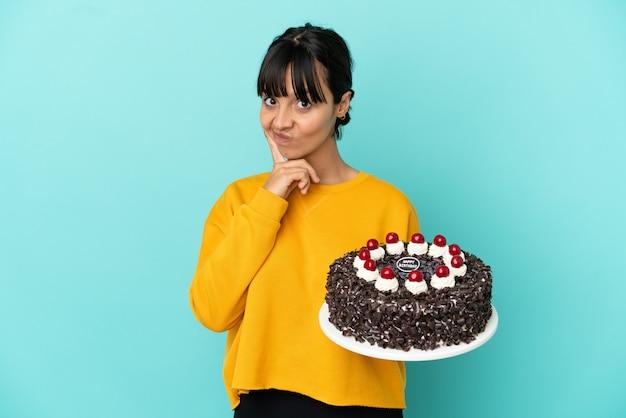 Молодая женщина смешанной расы держит торт ко дню рождения и думает
