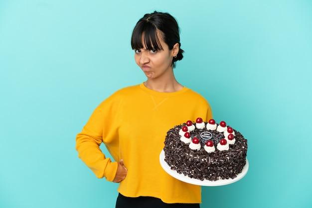 Молодая женщина смешанной расы держит торт ко дню рождения сердитый