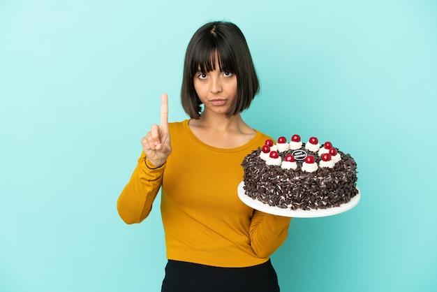 Молодая женщина смешанной расы держит торт ко дню рождения, считая один с серьезным выражением лица