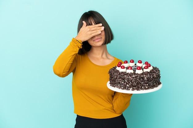 Молодая женщина смешанной расы, держащая день рождения торт, закрывая глаза руками. не хочу что-то видеть